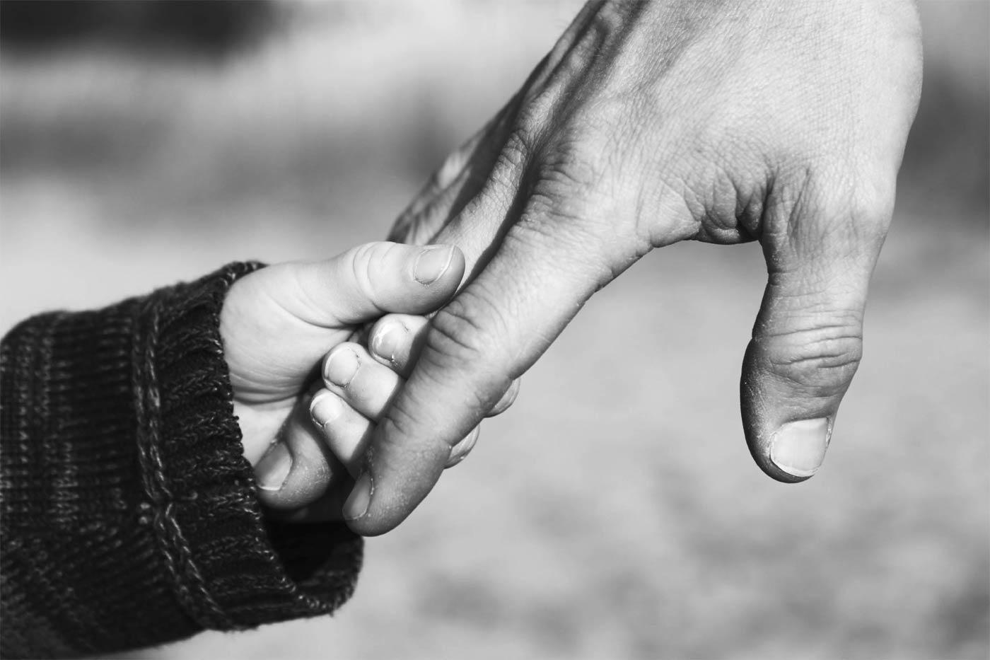 Ouder en kind die elkaar hand vasthouden